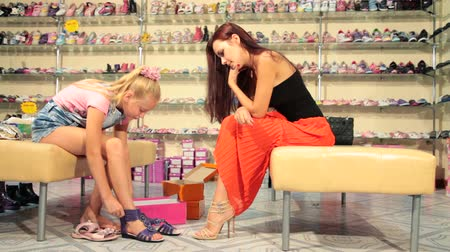 ayakkabı : Mother and daughter trying on summer footwear in shoe store