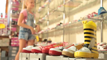 sapato : Little girl choosing summer footwear in shoe store, edited sequence
