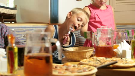 наслаждаться : Children eating pizza in italian restaurant