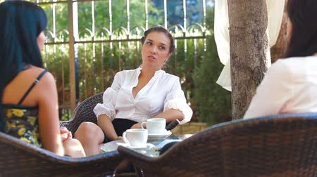 people talking : Female friends immersed in conversation at urban cafe Stock Footage