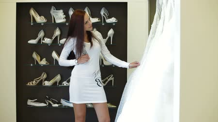 подвенечное платье : Young attractive woman choosing wedding dress in bridal boutique
