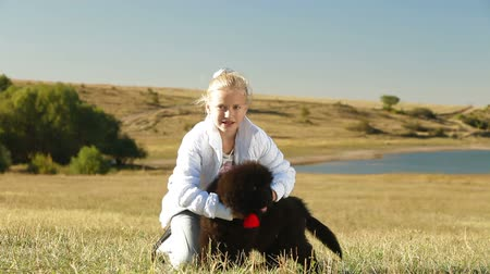 rescue dog : Little Girl Feeding Puppy Newfoundland