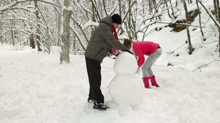 kardan adam : Winter holidays in a snowy forest, teenage couple making a snowman
