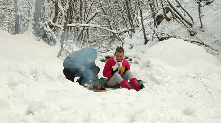 şenlik ateşi : Teenage Couple Enjoying Winter Holidays by Bonfire in Snowy Forest
