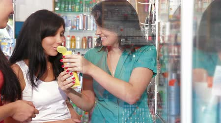 şampuan : Friendly shop representative offers goods to a buyer in the cosmetics department