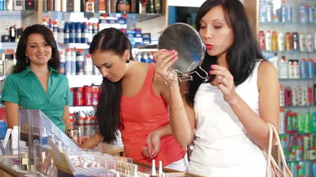 ruj : Female Friends Testing Lipstick in Beauty Department