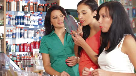 ruj : Female Friends Testing Lipstick in Cosmetics Store