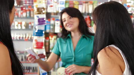 dialog : Young women shopping in cosmetics store, shop assistant offers goods for body care