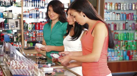 pomocník : Sales Persons Assisting Female Shoppers in Choice of Cosmetics