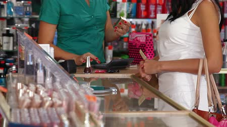 продукты : Woman paying for beauty care products at the cash counter