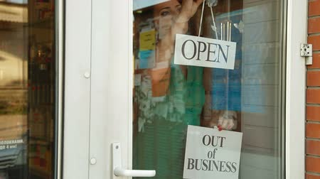 proprietário : Business owner puts up Out Of Business sign on door of her store, medium shot