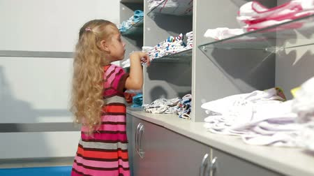 покупка товаров : Little girl shopping for girls clothes in a clothing store, looking kids underwear
