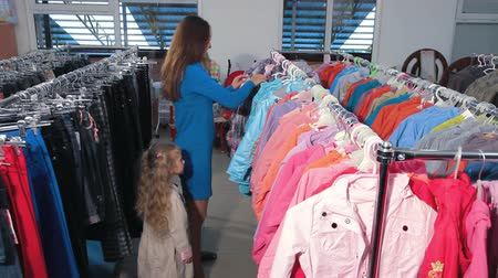 ceket : Mother and daughter shopping for clothes in a clothing store, choosing jacket Stok Video