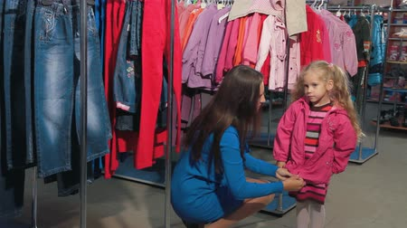носить : Mother and daughter shopping for clothes in a clothing store, happy child kissing mother