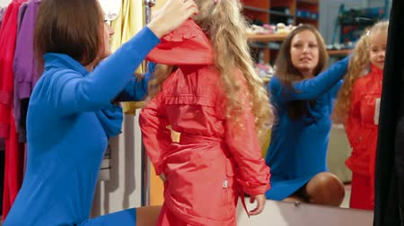 stílus : Mother and little daughter shopping for girls clothes in a clothing store, trying on raincoat