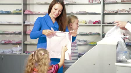 calcinhas : Mother with two daughters shopping for girls clothes in a clothing store, looking kids underwear Vídeos