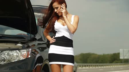 poškozené : Woman having car troubles on the road, calling on the cell phone for emergency repair service