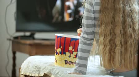 girl : Little blonde girl eating popcorn and watching 3D movie at home, rear view Stock Footage