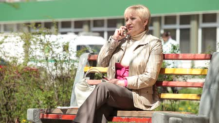 пенсионер : Senior lady talking on the phone outdoors