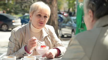 positive ageing : Smiling Senior Women Eating Dessert At Outdoor Cafe Stock Footage