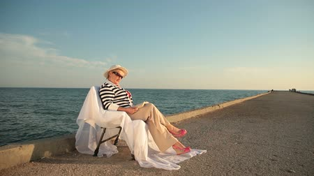 utazó : Retired woman relaxing with book at seaside
