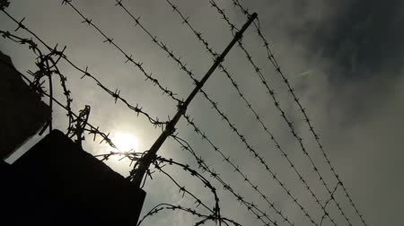 farpado : Fence with barbed wire surrounding secured property. Pan shot Stock Footage