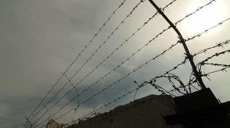 фехтование : Fence with barbed wire surrounding secured property. Pan shot Стоковые видеозаписи