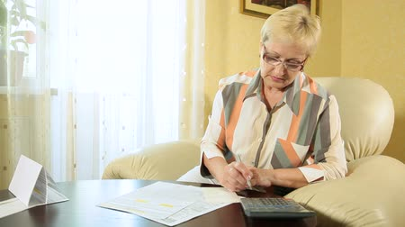 důchodce : Mature woman filling out tax form