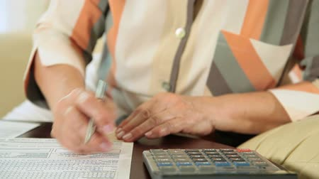 daň : Hands of mature woman fills out tax forms