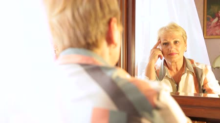 looking : Senior woman looking into mirror Stock Footage