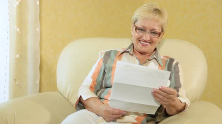 positive ageing : Cheerful senior woman reading some financial paper