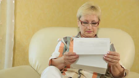 letras : Mature woman looking at a bank statement
