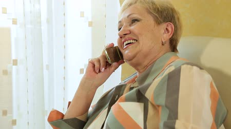 senior lifestyle : Mature woman chatting on the phone at home closeup Stock Footage