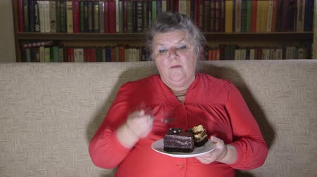 sitting room : Overweight senior woman sitting on a couch in front of the TV and eating cake