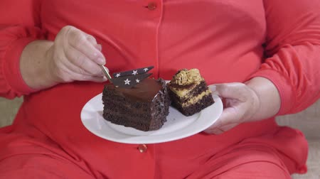 tłuszcz : Overweight mature woman sitting on a couch and eating cake