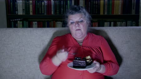 novela : Fat senior woman watching tv show and eating cake at night Stock Footage
