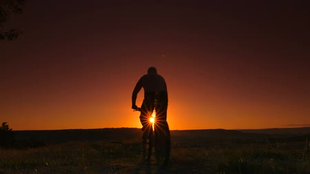 bisiklete binme : Silhouette of bicyclist against sunset. Rear view, Canon C100