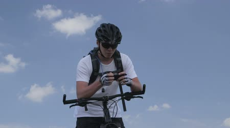 gotículas : Mountain biker looking for route on smartphone Stock Footage