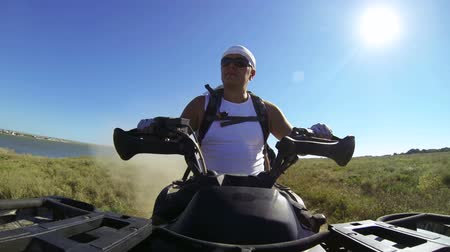 четыре человека : Man riding quad bike on a dusty road along the coast. Front view, GoPro Hero3 BE Стоковые видеозаписи
