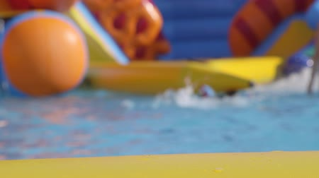 inflável : Kids playing in inflatable water slide with pool, out of focus