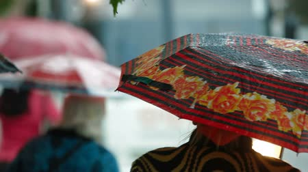andar : People with umbrellas waiting at the bus stop under rain Vídeos
