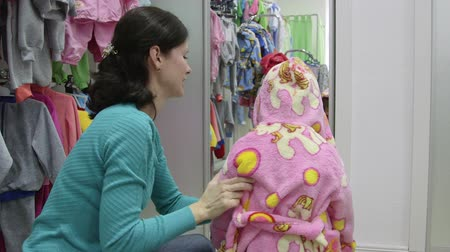 housecoat : Mother with child trying on dressing gown in clothing store