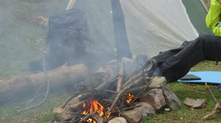 hátizsákkal : Woman backpacker sitting by campfire at campground, using smartphone