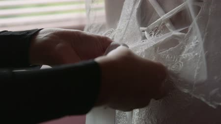 подвенечное платье : Bridesmaid helping bride with wedding dress closeup