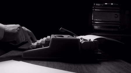 roman : Journalist typing on a manual vintage typewriter, film noir style
