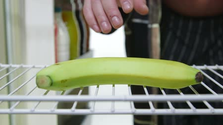 lodówka : Fat man takes out banana from an empty fridge closeup