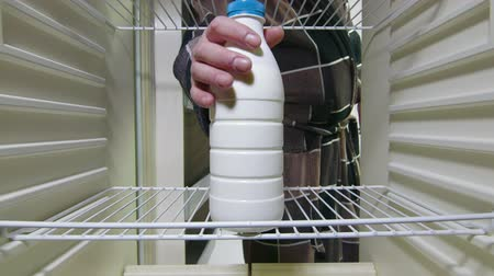 lodówka : Man takes out milk bottle from the refrigerator