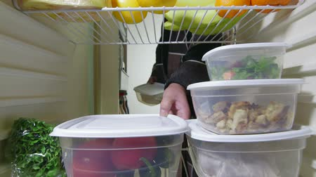 DOLLY: Man takes out stack of food from fridge Stock Footage