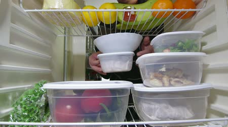 lodówka : Man takes out stack of food plastic containers from fridge, view from inside