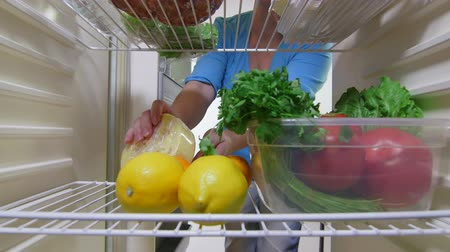 hűtőgép : Housewife fills food into refrigerator, inside view timelapse